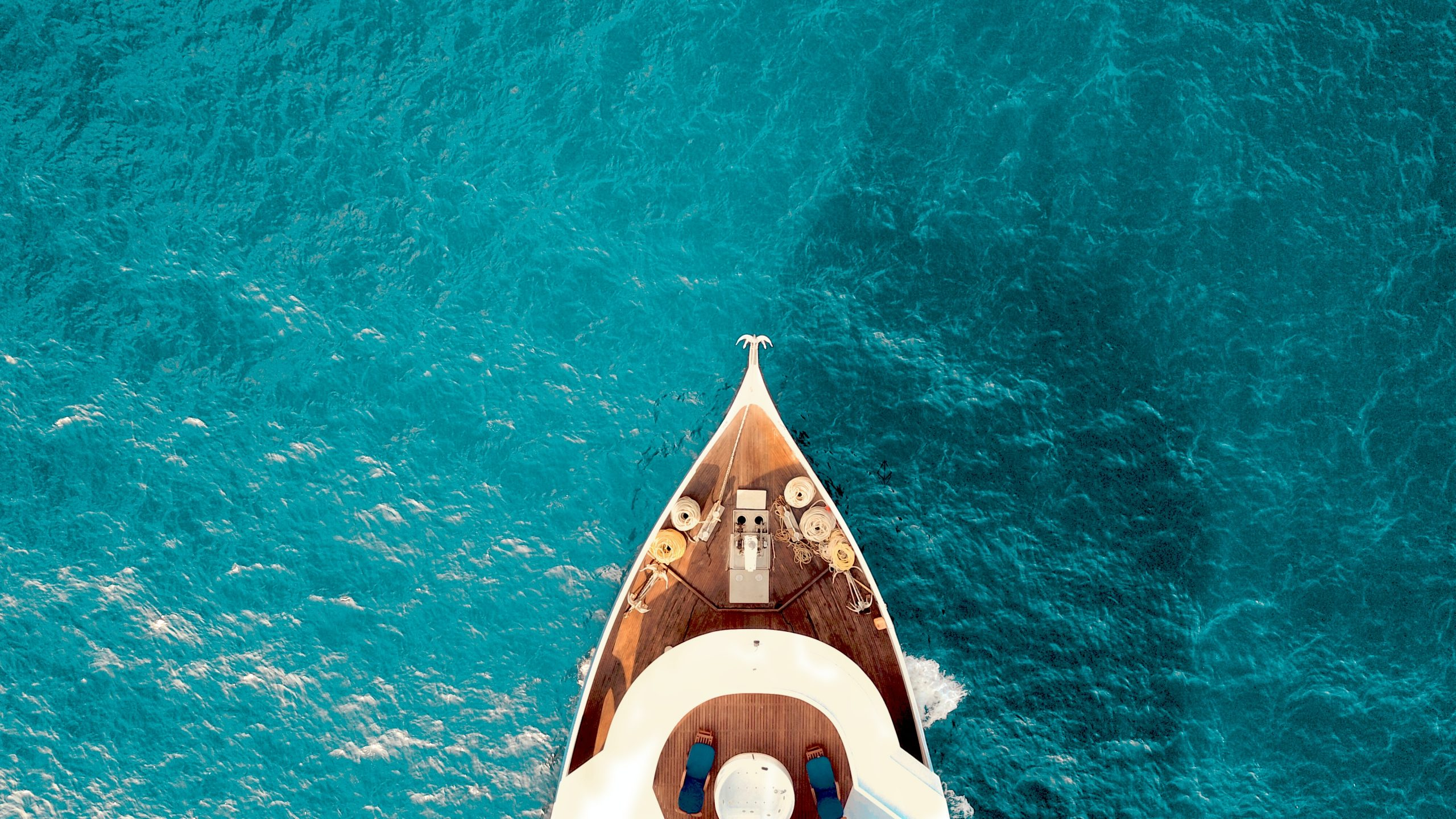 A large white yacht against a clear ocean.