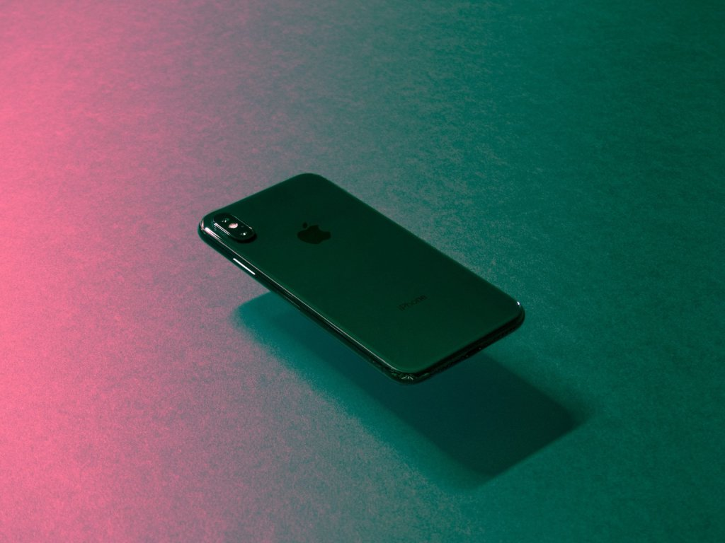 A phone floating on a pink and green background.