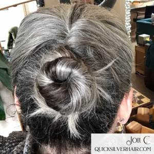 Image of woman with silver hair in a half twisted bun
