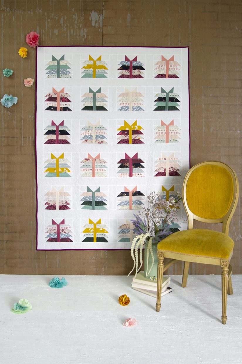 Quilt on a wall with a yellow chairin front of it. The quilt has colorful fabric bundles tied with ribbons