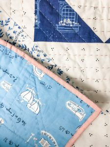 The corner front and back of a Vienna Quilt, showing the hand quilting on the quilt and the quilt binding