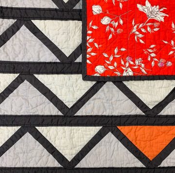 Grey, Black and orange fabric that make a Cafe Tiles Quilt and Backing