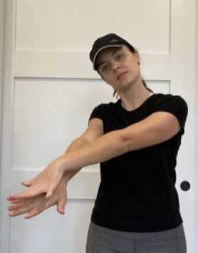 Elizabeth Chappell in a black hat and black shirt stretching her neck
