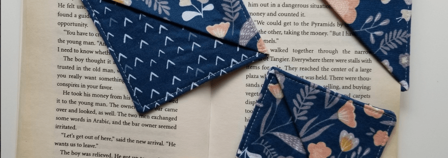 3 fabric book marks made of blue fabric, one being used to hold a book's spot