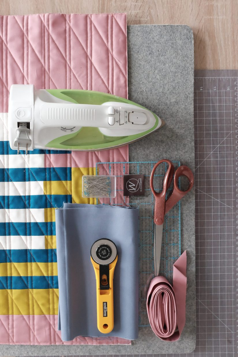An iron, scissors, rotary cutter, fabric, and a pressing mat