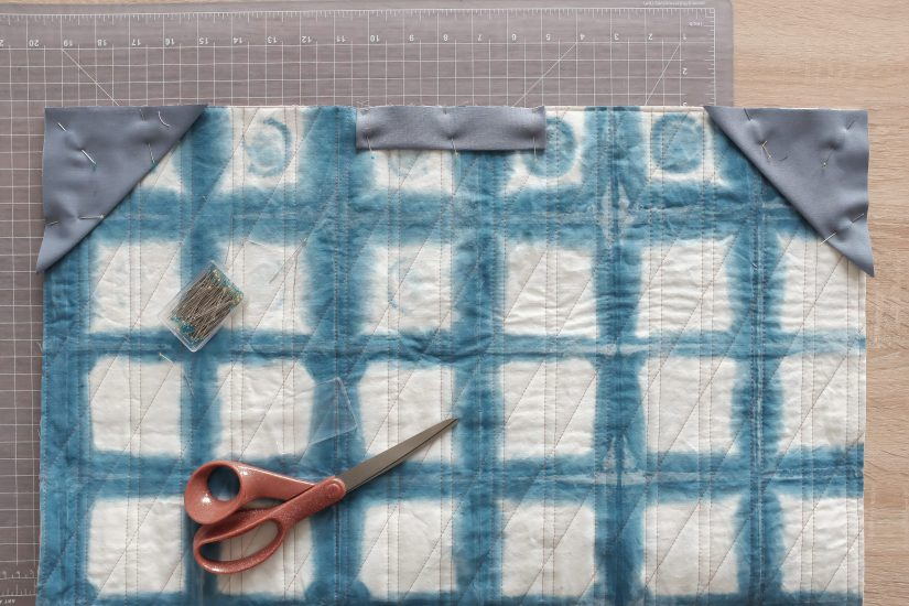 Blue and white tie dyed fabric with grey fabric pinned to the corners.