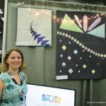 Renee with her quilts Flying North and Crystal City in the Massdrop booth at Quiltcon!