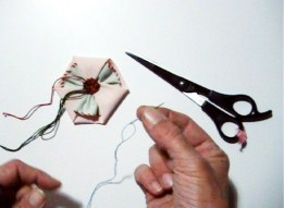 """As you can see perhaps, the red thread is sort of on the other side of the center - easy, because it was already attached to a needle. I could do the same with each green thread, but I'm lazy ;) Crochet hooks are too thick or too fine to do the job, so I """"invent"""" a tool for pulling the bundle through at once: an embroidery needle (best with ballpoint, to prevent injury - or just be careful) with a piece of sewing thread."""