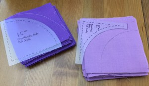 Stacks of fabric squares with marking traced on them