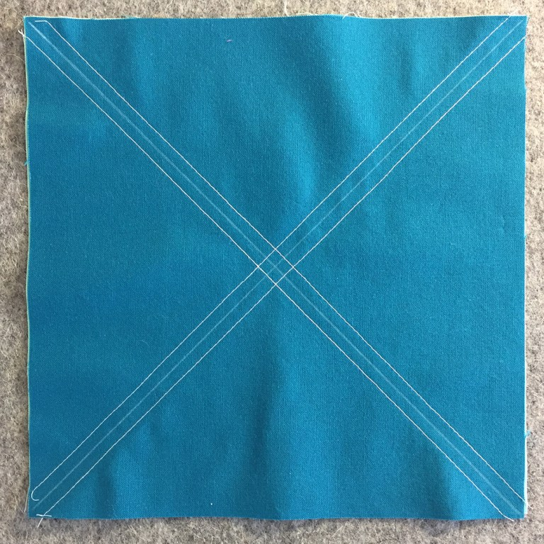 "Two 8"" squares of fabric sewn diagonally with four seams"