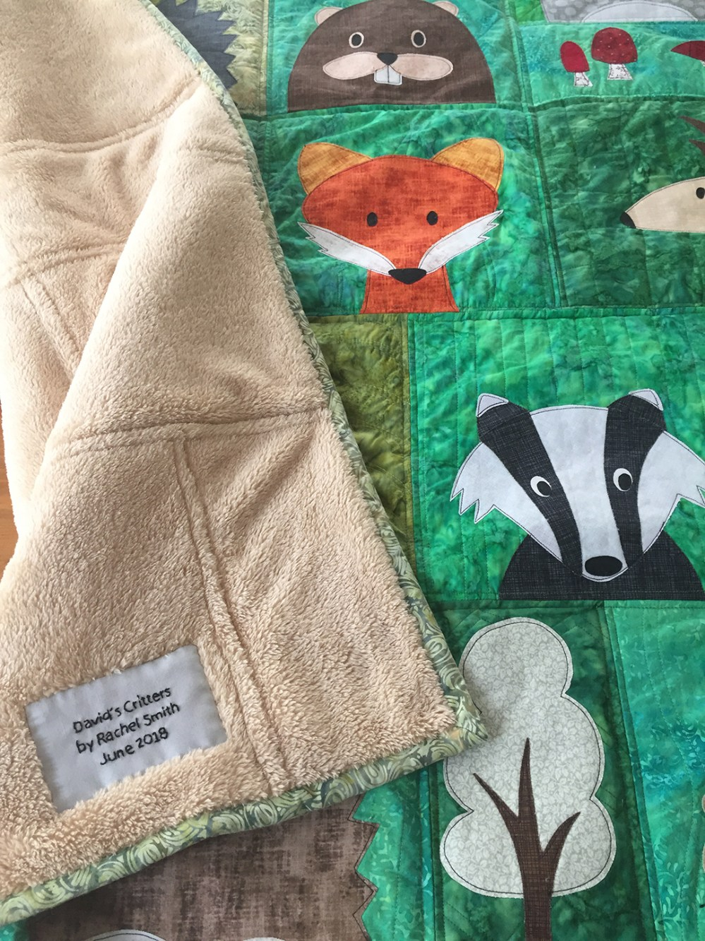 photo of a quilt showing a corner of the backing with an embroidered label