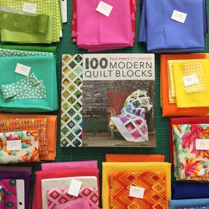 The City Sampler book surrounded by piles of coordinating fabric