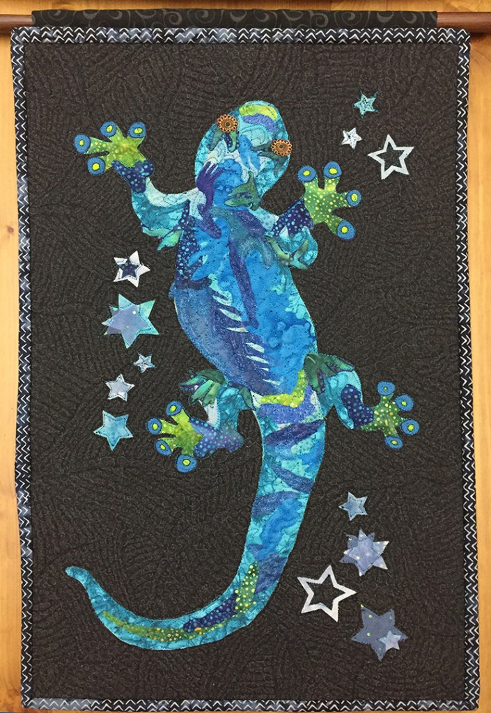 wall hanging of a blue gecko on a black ground