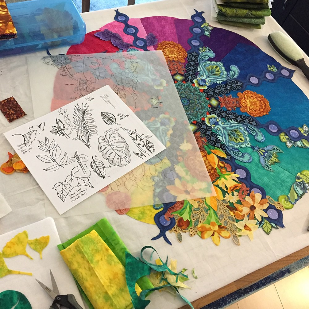 Table covered with sketches, scraps of fabric, and an in-progress quilt