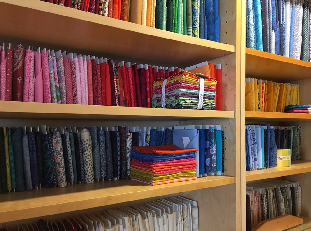 fabric lined on a shelf by color