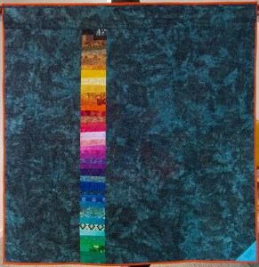 square teal quilt back with a rainbow stripe