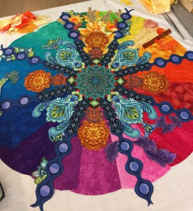 fabric collage showing yellow flowers in one ray of a colorful mandala