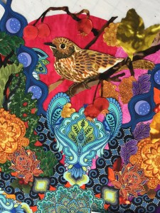 a fabric collage of a brown bird on a branch with some crabapples