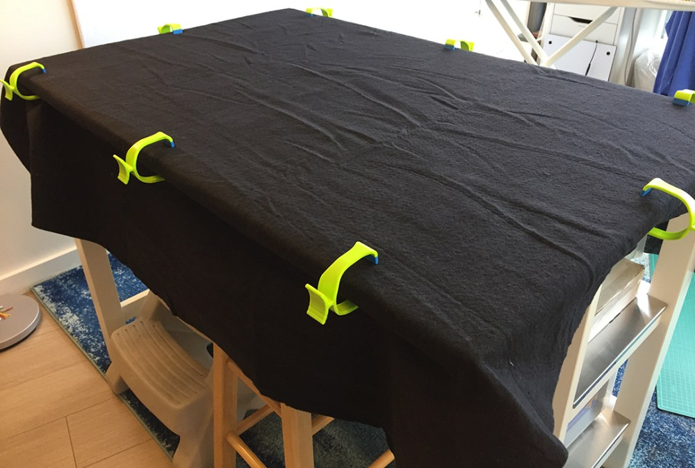 black quilt batting clamped to a table with the backing underneath