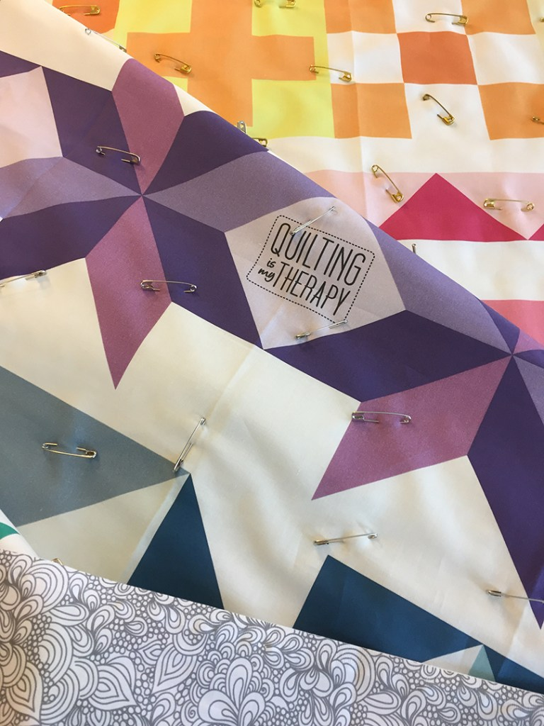 a quilt that has been sandwiched and pin basted, shown in folds