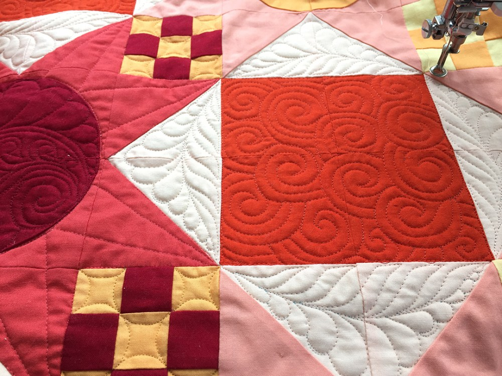 a close up of a quilt showing swirls and feathers