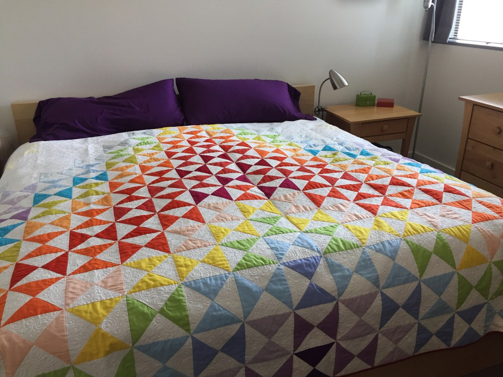 rainbow colored quilt on a bed