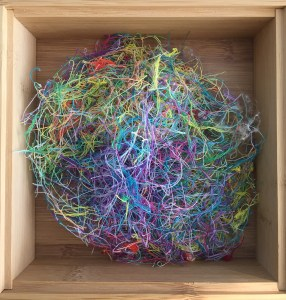 a pile of colorful clipped threads in an open wooden box