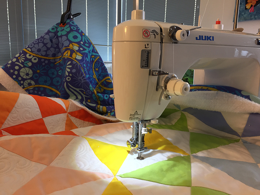 quilt in a machine with bungee clamp in the background