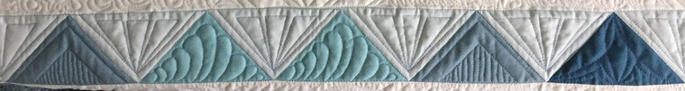 a row of quilted blue triangles