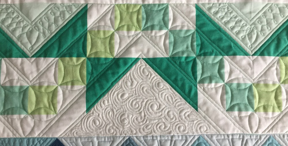 green and white quilt blocks with complex quilting