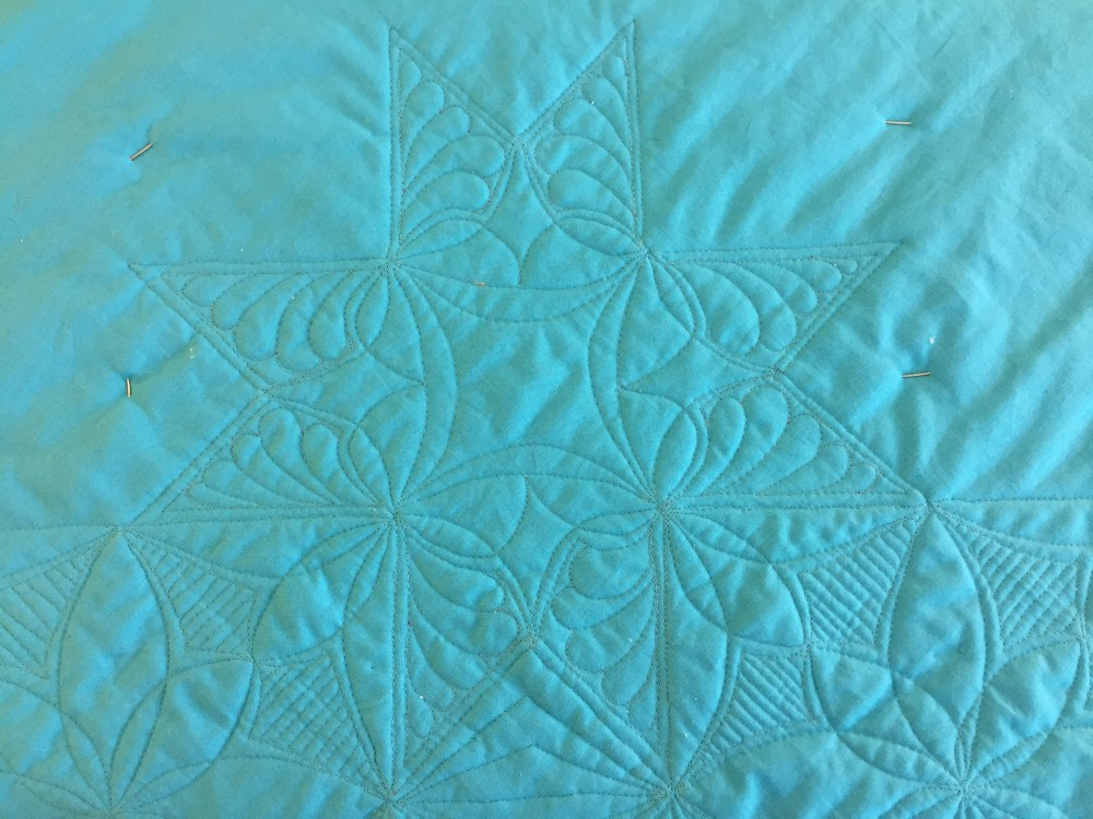 a blue quilt back with a star-shaped quilting design on it