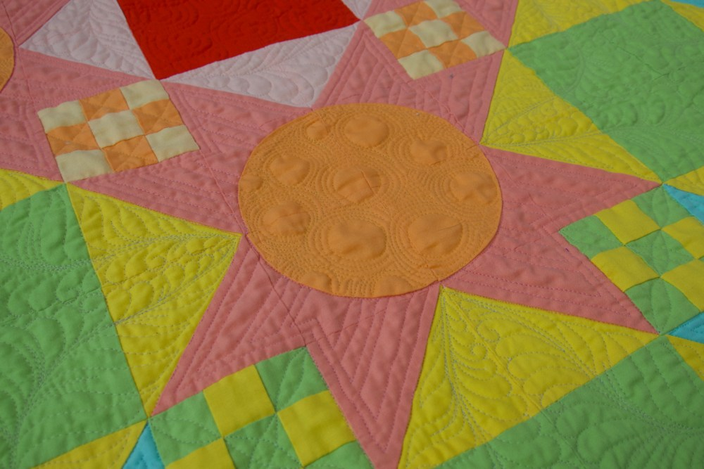 detail of a quilt with brightly colored blocks