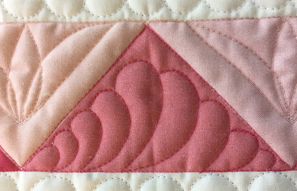a pink triangle quilted with feathers