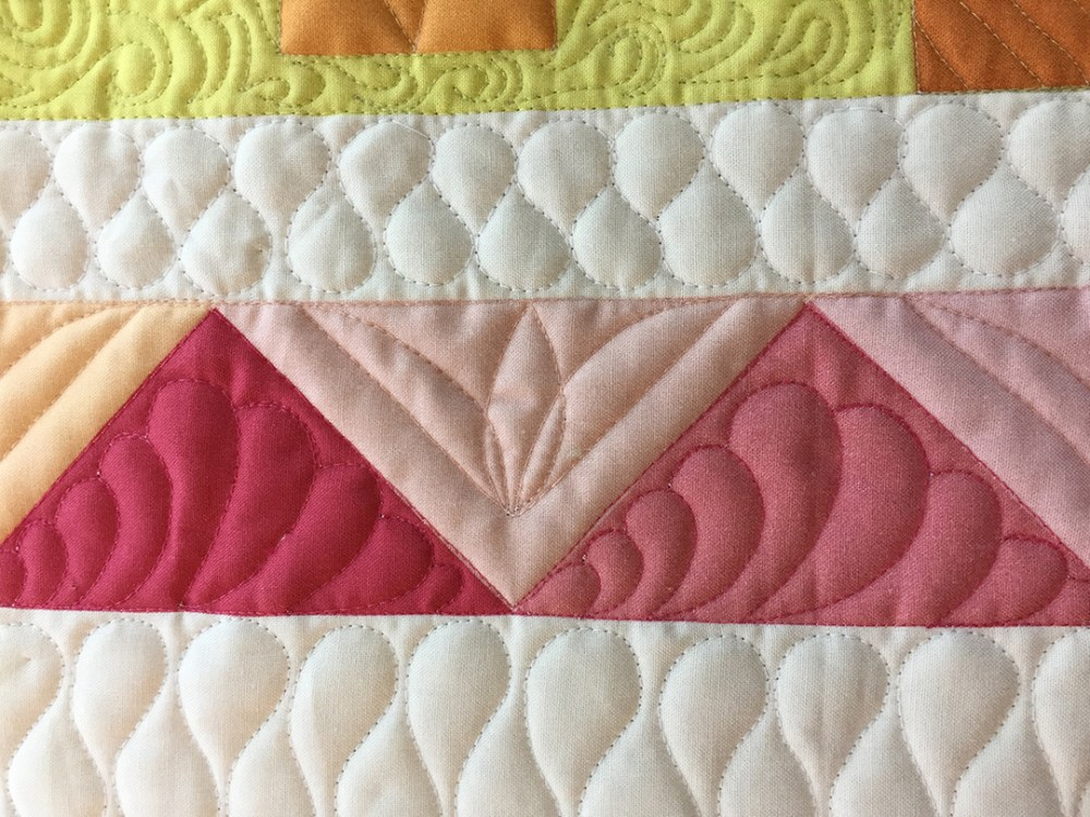 pink flying geese blocks quilted with feathers and flowers