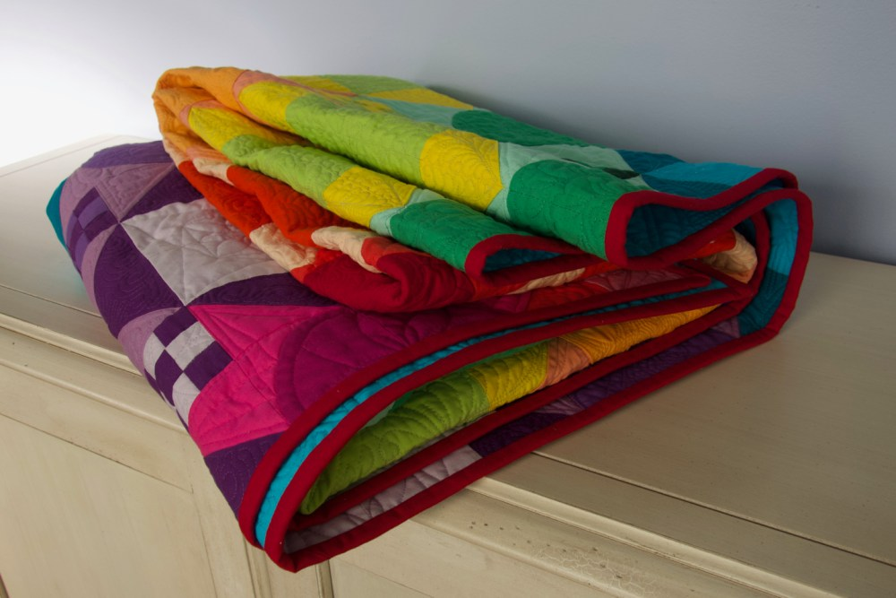 a colorful quilt folded on a dresser with the red binding showing