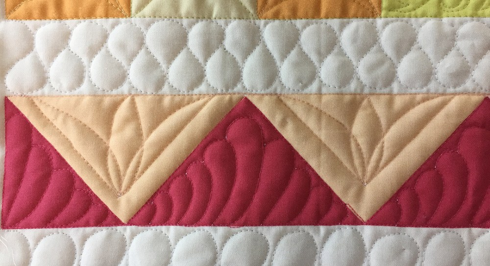 triangle blocks with quilted feathers and flowers