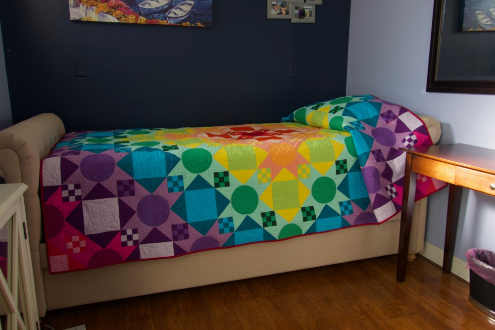 a daybed made up with a bright colorblock quilt