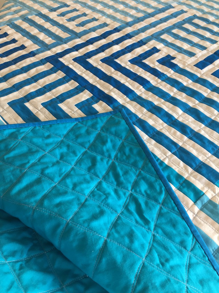 a blue and white striped quilt with a blue backing