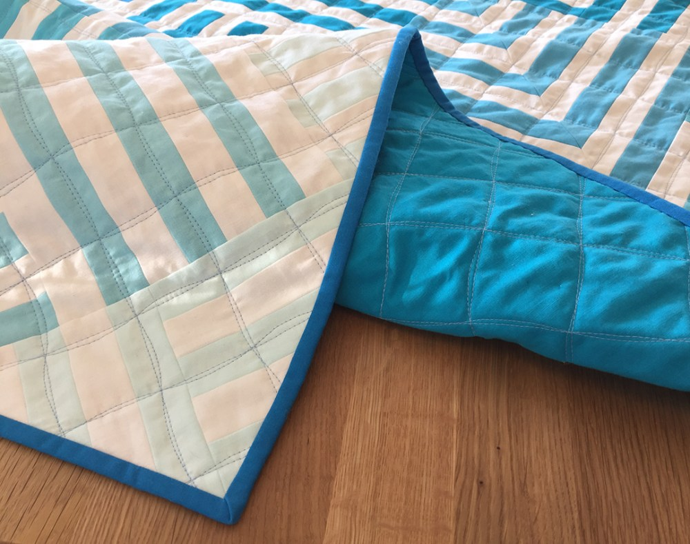 a blue and white striped quilt on a table