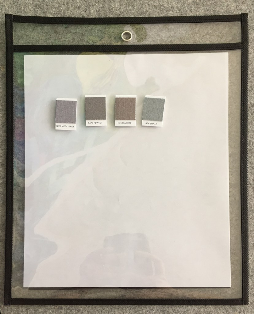 a magnetic sheet inside a dry erase pocket with four gray swatch magnets on it