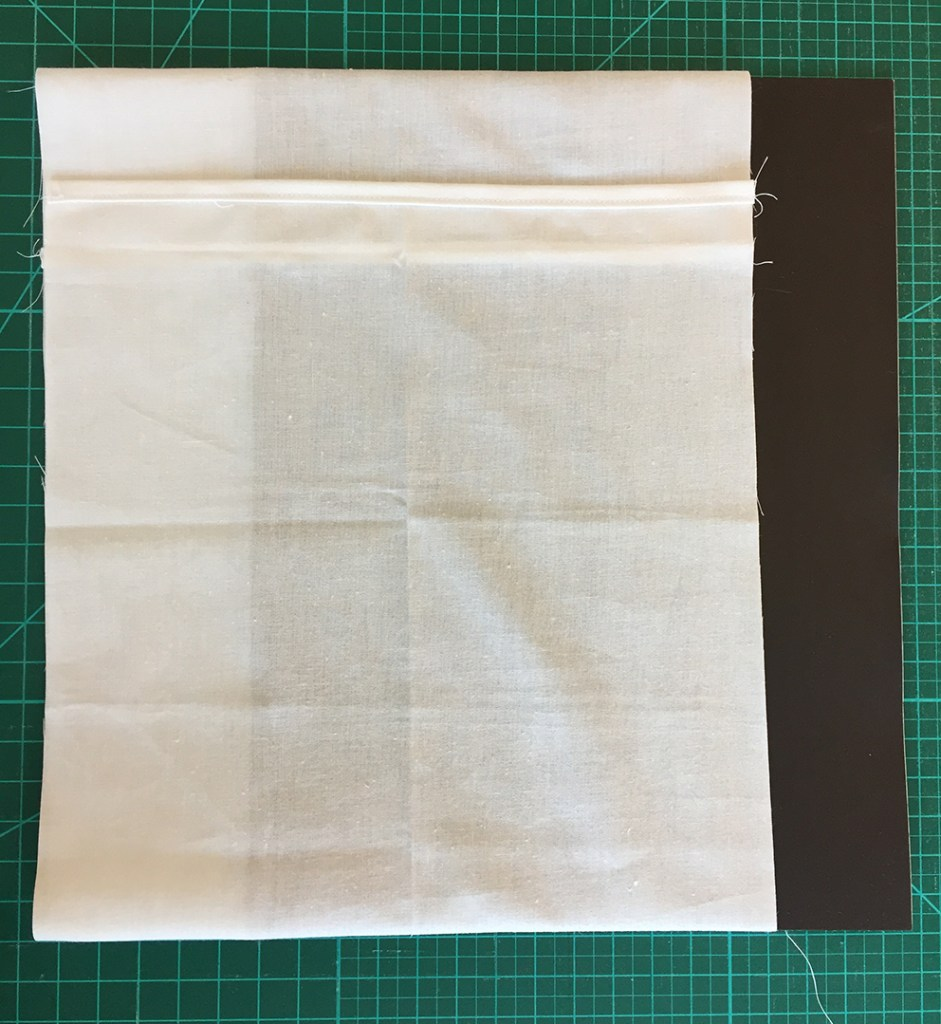 a folded piece of fabric with a flexible magnetic sheet partially inside the fold