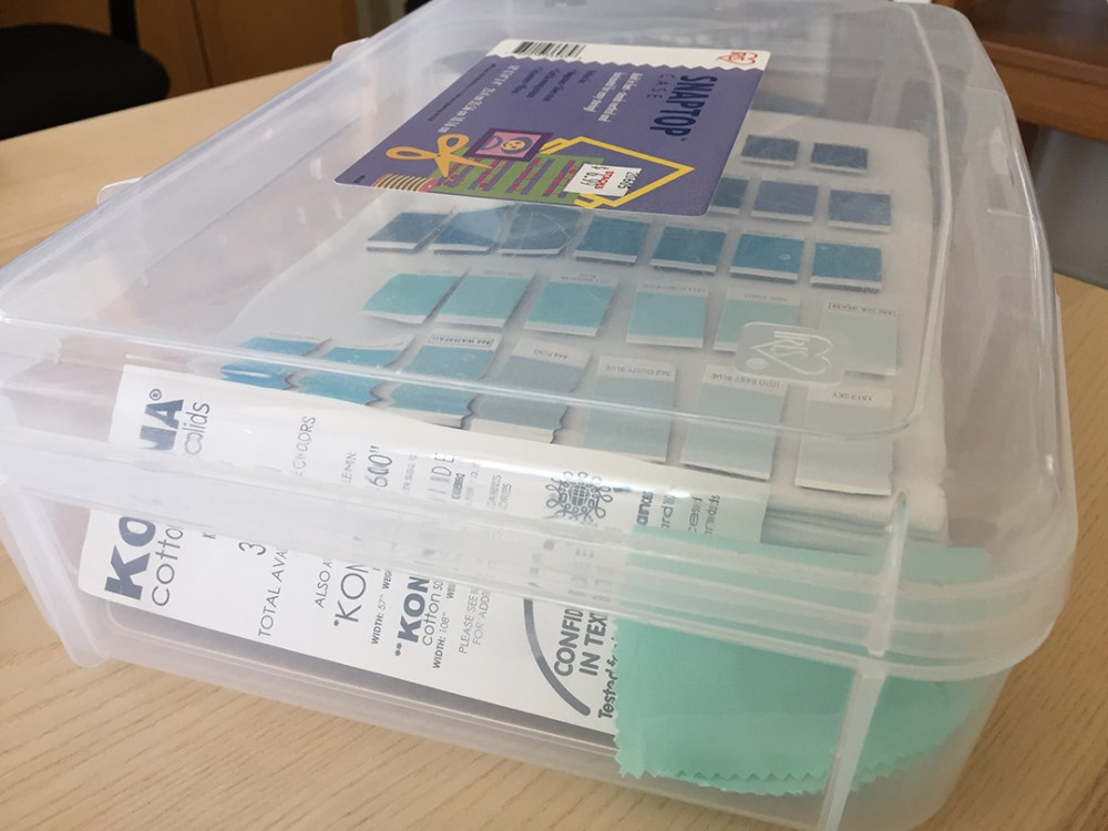 a closed plastic case with a swatch of fabric, a card with the fabric manufacturer's name, and a stack of magnetic swatch boards inside