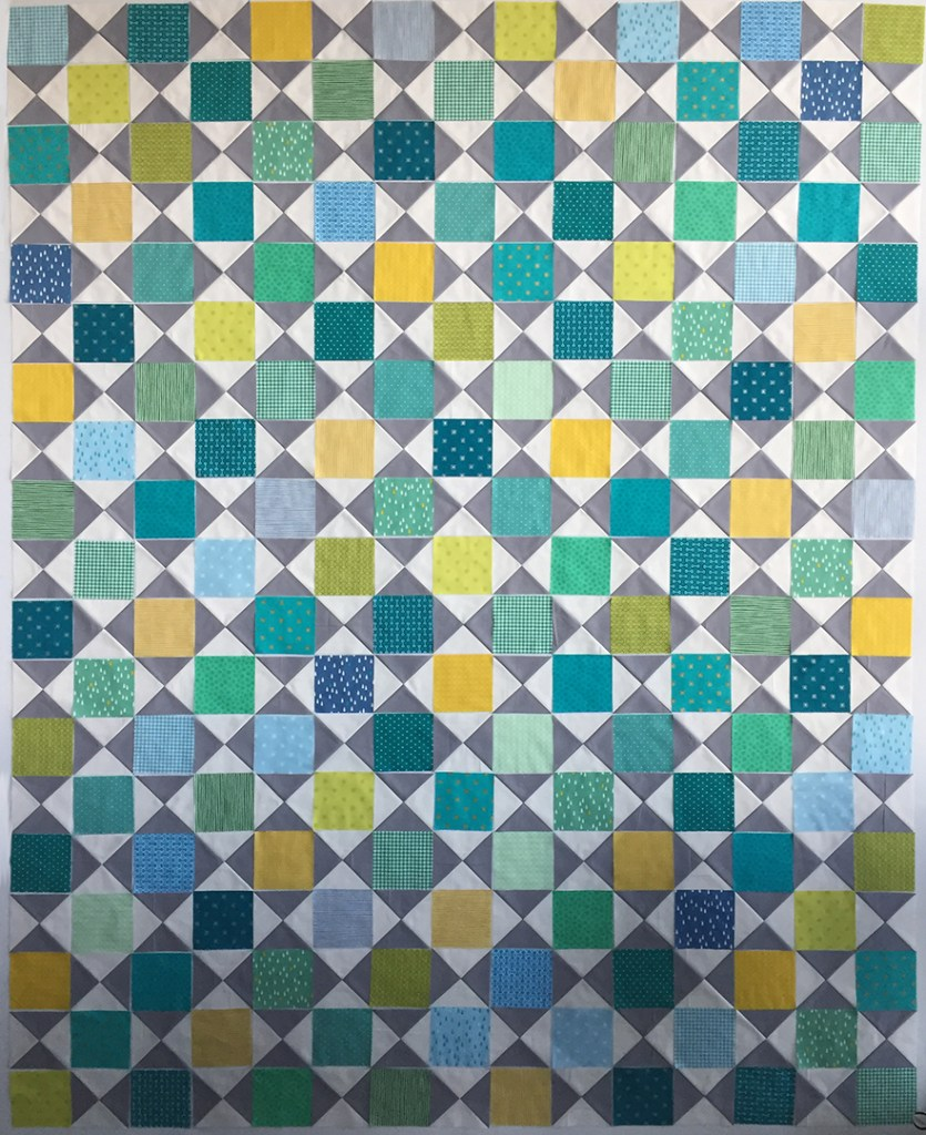 Quilt blocks in white, grey, green, and yellow laid out on a design wall