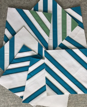 Stack of striped quilt blocks in white, blue, and green