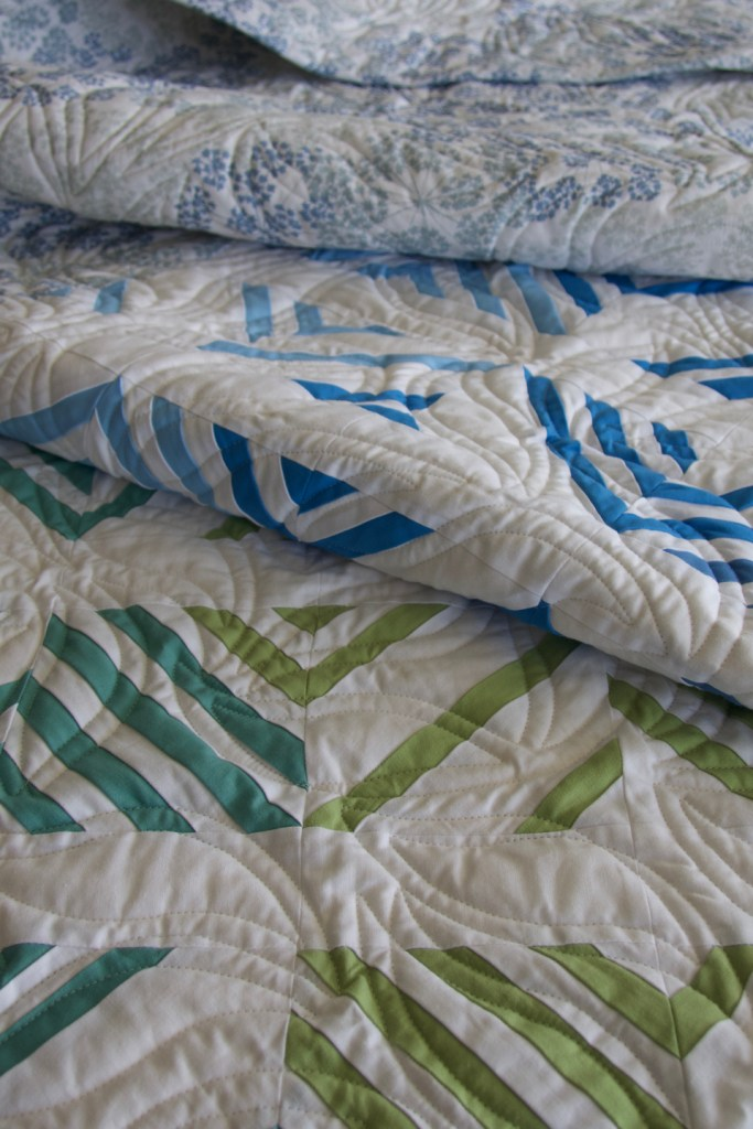 surface of the quilt, loosely folded, showing blue or green and white striped blocks and the leafy quilting pattern
