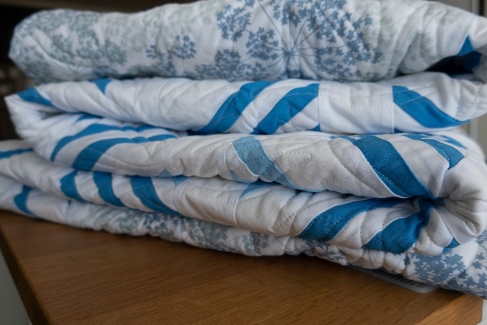 a blue and white quilt folded up on a table
