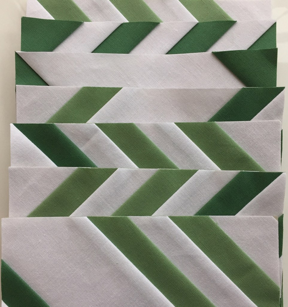 a stack of green and white striped paper-pieced blocks