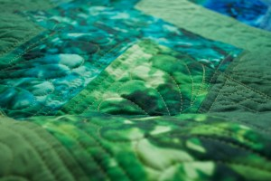 a close up of green quilted blocks
