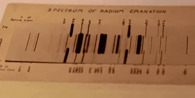 El espectro de emisión de radón, fotografiado por Ernest Rutherford en 1908. Los números al lado del espectro son longitudes de onda. El espectro medio es de emanación de radio (radón), mientras que los dos exteriores son de helio (añadido para calibrar las longitudes de onda).