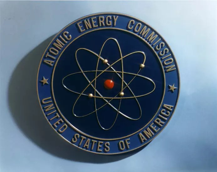 Escudo de la Comisión de Energía Atómica de los Estados Unidos, basado en el modelo atómico de Rutherford